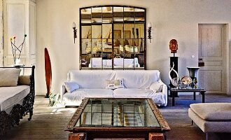 Coffee table with framed mirror as top, sofa with white, loose cover and panel of many individual mirrors on wall