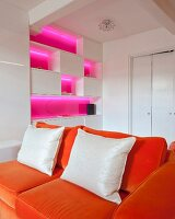 Fitted cabinets with shelf compartments illuminated bright pink behind orange sofa in white interior