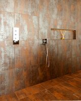 Spacious, floor-level shower with niche shelf and rust-effect tiles