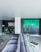 Grey three-seater sofa with narrow glass table against backrest in spacious living room with large painting of forest on wall