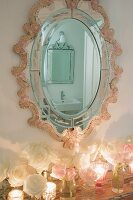 Romantic, ornate oval mirror reflecting bathroom above arrangement of roses and tealight holders