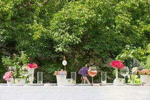Table set for afternoon coffee with glasses an flower arrangements