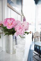 Peonies in tin can against wooden wall