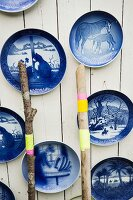 Blue, vintage decorative wall plates on white board wall
