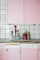 Kitchen counter with pink cabinets and concrete worksurface