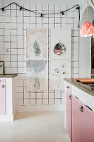 Framed pictures and fairy lights on white-tiled kitchen wall