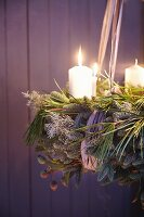 And Advent wreath made from green twigs and pine with white pillar candles