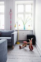Retro wooden tricycle and yellow standard lamp in front of window in corner of living room with rustic wooden floor
