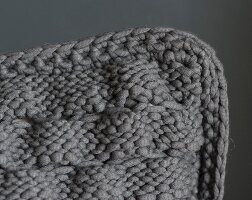 A cushion cover with a knitted now that pattern and a crocheted edge (seen from above)