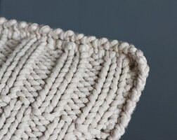 A knitted cushion with an offset ribbed pattern and a crocheted edge (detail)