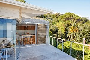 Spacious terrace adjoining house with view into kitchen through open sliding door; tropical forest in background
