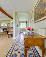 Pale, wooden antique console table in open-plan hallway with tiled floor and arched doorway