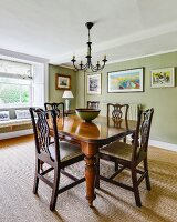 Antique dining table and chairs with carved backrests in green-painted dining room with sisal carpet