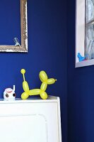 Yellow balloon-dog ornament in front of royal blue wall