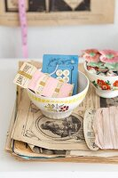 Still-life arrangement of French bowls and vintage sewing utensils on stack of antique magazines