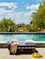 Floor cushions and scatter cushions on wooden pallet next to pool