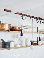 Bulb-style pendant lamps with cords wrapped around copper pipe in front of pans and glasses on wall-mounted shelves