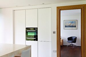 White fitted kitchen cupboards with integrated oven next to open door with view of black swivel chair