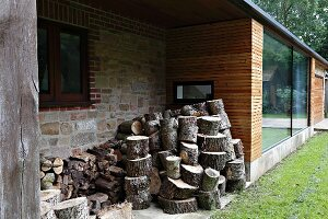 Firewood stacked in façade niche of modern house with wooden cladding and stone walls