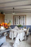Dining area in front of large picture of cutlery on wall; fruit basket on kitchen counter in foreground