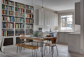 Square rustic wooden table, vintage chairs and bookcase in front of white fitted kitchen with panelled doors