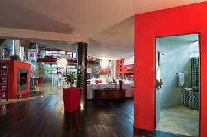 White and red furnishings in loft apartment with view into concrete-effect bathroom