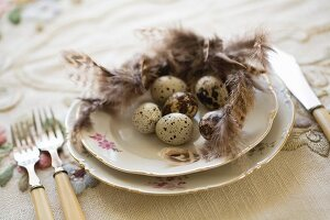 Quail eggs and feathers on floral gold-rimmed plate and vintage cutlery