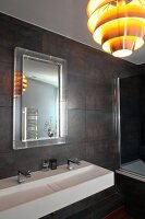 Modern bathroom with dark wall tiles, white designer sink with twin taps and retro pendant lamp