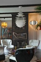 White leather armchairs and classic pendant lamp in front of metal fireplace in cosy retro interior