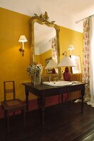 Washstand made from desk with integrated sink and elegant, gilt-framed mirror on yellow-painted wall
