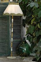 Vintage standard lamp with fabric lampshade and green demijohn next to climbing plant