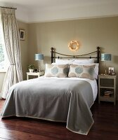 Elegant traditional bedroom; double bed with metal frame and grey bedspread below fairy light wreath on grey-painted wall