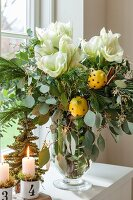 Festive bouquet with white amaryllis and clove-stuffed lemons in glass vase