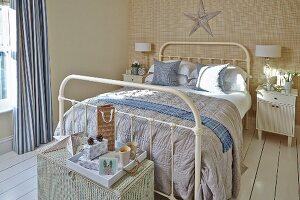 White, metal double bed and tray on wicker trunk in rustic bedroom