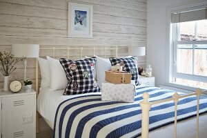 Double bed with white metal frame and white-and-blue striped bedspread in rustic bedroom