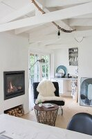 View across desk to black easy chair with white sheepskin and wire-framed side table in front of fireplace