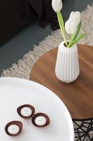 Tealight holders and tulips in white retro vase on round side tables