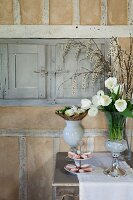 Vase of white tulips and biscuits on cake stand on console table against rustic wall