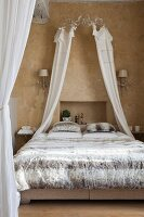 Double bed with unusual bed linen, crown and canopy in Mediterranean interior