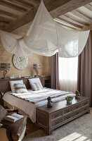 White fabric canopy hung from wood-beamed ceiling above double bed in elegant bathroom