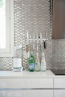 Metallic wall tiles and knives on magnetic strip above kitchen counter