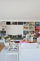 White sofa, armchairs, table and large bookcase with bench integrated into niche in background