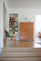 Simple armchair and pale wooden chest of drawers on raised platform