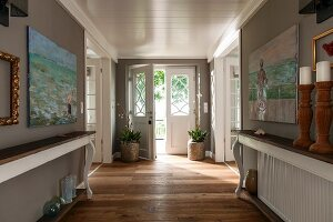 Console tables with curved legs against grey-painted walls in foyer of country house