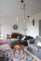 Retro side table and seating with grey upholstery in simple living room with bare bulbs hanging from white wood-beamed ceiling