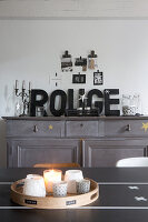 Tealights and candles on table in front of decorative letters on grey sideboard and collage of postcards on wall