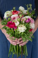 Hands hoolding bouquet of ranunculus and anemones