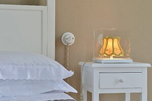 Lit, vintage bedside lamp in glass case on white bedside table with drawer