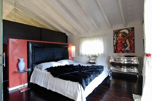 Bedroom with red partition behind bed headboard, silver chest of drawers and modern painting