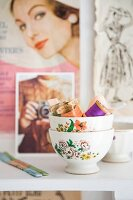 Sewing utensils in bowls with floral motifs in front of old fashion photographs
